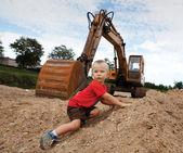 Boy and escavator — Stockfoto