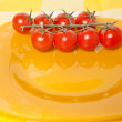 Cherry tomatoes on a branch on a yellow plate — Stock Photo #67764711