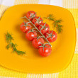 Cherry tomatoes on a branch on a yellow plate — Stock Photo #67764789