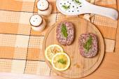 Cutlet with lemon slices on a cutting board next to the saucepan — Foto Stock