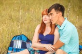 Beautiful young couple sitting in the field; outdoors — Stock Photo