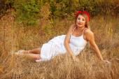 Beautiful young woman posing lying in grass outdoors — Stock Photo