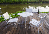 Garden chair and table with riverside — Stock Photo