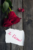 Three red roses on rustic table with handwritten words je t'aime — Stock Photo
