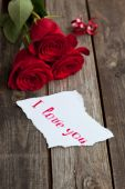 Three red roses on rustic table with handwritten words I love yo — Stock Photo