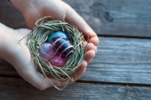 Easter decoration - glass eggs in hands — Stock Photo
