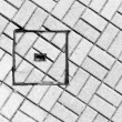 Abstraction of sewer manhole on floor with cobblestones — Stock Photo #57989101