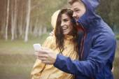 Couple looking weather forecast — Stockfoto