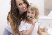 Mother teaches daughter to brush teeth — Fotografia Stock