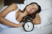 Woman in bed with alarm — Stock Photo
