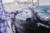 Adam bir araç sprey su ile yıkama — Stok fotoğraf