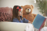 Girl with her teddy bear reads book — Stock Photo
