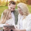 Happy family in park with tablet — Stock Photo #75664461