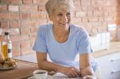 Mature smiling woman in kitchen — Stock Photo