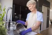 Zralá žena mytí hrnce — Stock fotografie