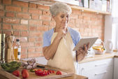 Mature woman looking recipe on tablet — Stock Photo