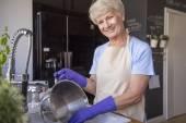 Grandmother washing saucepan — Stock Photo