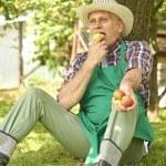 Gardener sitting under apple tree — Stock Photo #76162867