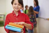 Boy standing with books primary school — Stock Photo