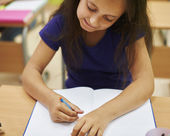 Little girl writing on lesson — Stock Photo