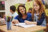 Teacher helps girl writing lesson — Stock Photo