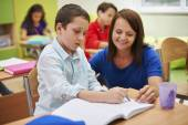 Teacher helping her pupil — Stock Photo