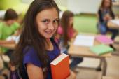 Female pupil standing with book — Stock Photo