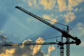 Construction cranes against of the sun — Foto de Stock