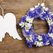 White wicker wreath decorated with flowers, and wooden angel win — Stock Photo #59846237