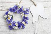 Wicker wreath decorated with cornflowers and chamomiles, and woo — Stock Photo