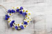 White wicker wreath decorated with cornflowers and chamomiles — Stock Photo