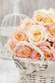 Wicker basket of roses on rustic wooden table. — Stock Photo