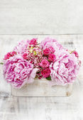 Pink peonies and roses in wooden box. — Stock Photo