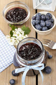 Jar of blueberry jam decorated with blue bow — Stock Photo