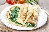 Mediterranean cuisine: crepes stuffed with cheese and spinach — Stock Photo