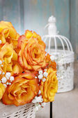 Bouquet of orange roses in a white wicker basket and vintage bir — Stock Photo