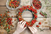 Florist at work: woman making rose hip and hawthorn wreath — Stockfoto