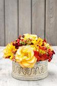 Bouquet of orange roses and autumn plants in vintage ceramic vas — Stock Photo