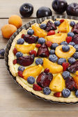 Sweet tart with peaches, plums and blueberries — Stock Photo