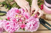 Florist at work: woman making floral decoration of pink peonies — Fotografia Stock