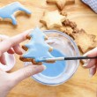 Decorating gingerbread cookies with blue and white icing. — Stock Photo #60186031