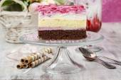 Layer cake with pink icing on a glass cake stand — Stock Photo
