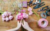 Florist at work. Woman making bouquet of pink persian buttercup — Stock Photo