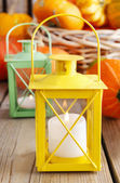 Beautiful lanterns and pumpkins on wooden table — Stock Photo