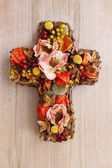 Cross made of artificial flowers and autumn plants. — Stock Photo
