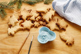 Decorating gingerbread cookies with blue and white icing. — Stock Photo