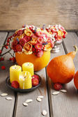 Autumn table decoration: bouquet in pumpkin and candles — Stock Photo