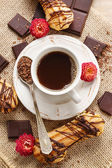 Cup of coffee, bar of chocolate and eclairs — Stock Photo