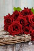 Bouquet of red roses on wooden table — Stock Photo