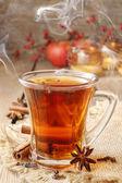 Glass of hot steaming tea among christmas decorations — Stock Photo